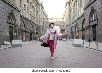 Excited mature lady enjoying walk in city