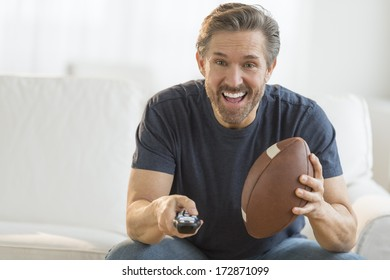 Excited mature man with American football watching TV on sofa