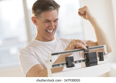 Excited mature man clenching fist while using balance weight scale at gym