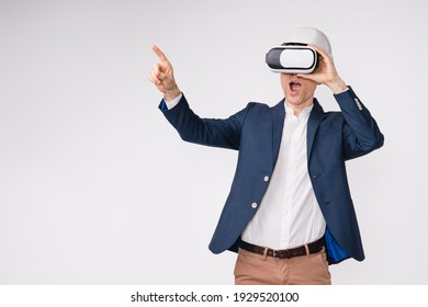 Excited mature man in formal outfit using VR-glasses and pointing at copy space isolated over white background