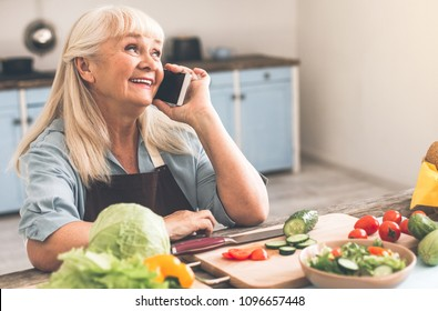 Excited mature woman is talking on mobile phone and laughing. She is sitting at table while cooking dinner in kitchen
