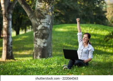 Excited mature woman wining holding fist up high screaming of happiness with laptop