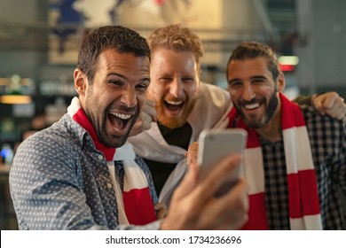 Excited men watching football in streaming on smartphone. Football fans watching game on phone and celebrating victory score at pub. Happy supporters cheering and exulting after winning an online bet.