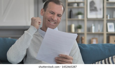 Excited Middle Aged Man Cheering while Reading New Contract