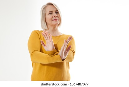 excited middle aged woman showing the sign of stop, neglect negation and reluctance
