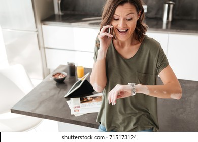 Excited middle aged woman talking on mobile phone and looking at her wrist watch while sitting on a table in a kitchen