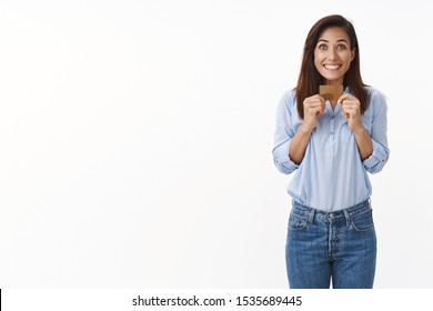 Excited middle-aged woman shopping, smiling broadly thrilled awesome sale week, give credit card make purchase, pay for product, grinning amazed, receive big cashback, stand white background