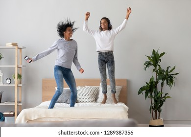 Excited millennial African American mother and daughter in headphones listen to music, jump on bed, happy black mom or nanny have fun with teen child, relaxing in bedroom enjoying tracks in earphones