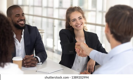 Excited millennial businesswoman handshake male business partner get acquainted at office meeting, smiling young female boss or ceo shake hand greeting with new employee at company briefing