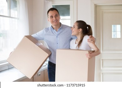 Excited millennial couple holding cardboard boxes entering modern bought house, happy husband and wife moving to own apartment, smiling young spouses start living together. New beginning concept