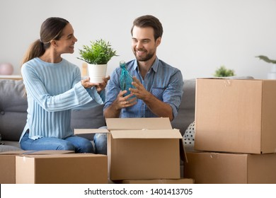 Excited millennial couple sit on couch unpack boxes settle in new home on moving day, happy smiling husband and wife unbox packages with personal belongings relocating to own apartment together