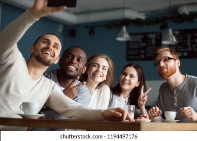 Excited millennial friends make selfie on smartphone having fun in coffeeshop, happy students smile for picture on phone meeting together in café, diverse young people posing for self-portrait
