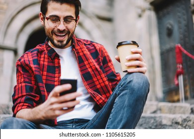 Excited millennial male getting message about victory in online lottery surprised with achievement outdoors, overjoyed young hipster guy happy about getting credit in banking via smartphone app