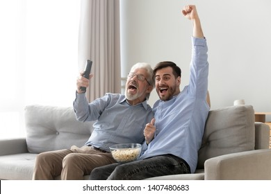 Excited millennial man and senior father sit on couch watching football game on TV raise hands cheering, happy elderly dad and young son relax on sofa support team enjoy match at home together