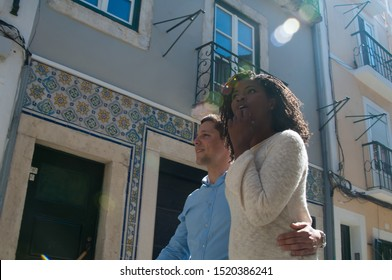 Excited mix raced couple spending weekend outside. Young man and woman walking in old town, hugging and looking away. Sightseeing concept