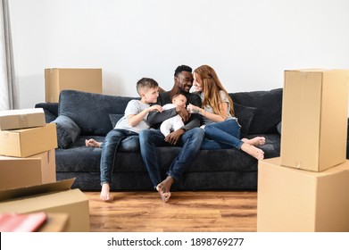 Excited mixed race family on relocation day. Overjoyed mother and father with two children sit on the sofa, smiling. Happy parents with son and daughter in new apartment, celebrate moving day