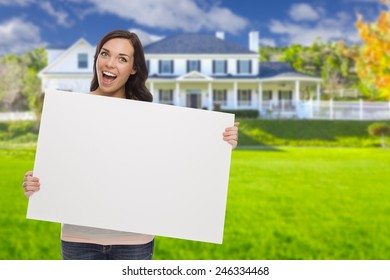 Excited Mixed Race Female with Blank Sign In Front of Beautiful House.
