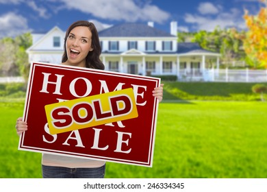 Excited Mixed Race Female with Sold Home For Sale Real Estate Sign In Front of Beautiful House.