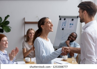 Excited mixed race girl employee get promotion feels happy handshaking with executive manager or company boss. Director greeting newcomer or congratulating successful worker with high rates at work