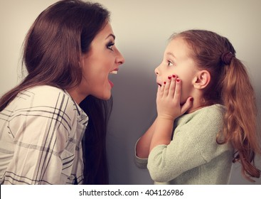 Excited mother and surprising kid girl looking on each other with opened mouth. Toned vintage portrait