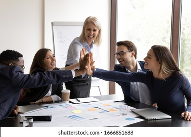 Excited motivated diverse businesspeople give high five show unity and support at company meeting, overjoyed multiracial coworkers engaged in teambuilding activity in office, collaboration concept