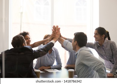 Excited multi racial businesspeople sitting at table conference room achieve corporate success celebrating market leadership giving high five hold hands together feels happy. Team spirit unity concept