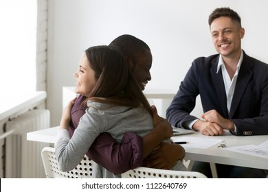 Excited multiethnic couple hugging after successful deal closing of house purchasing from smiling male realtor, biracial spouses congratulate with home buying after contract sign. Ownership concept