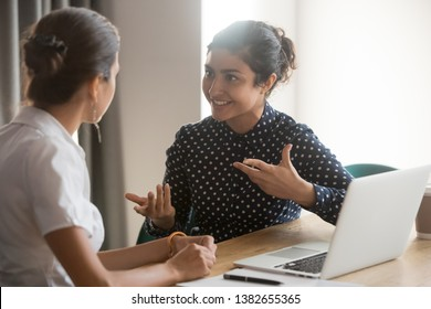 Excited multiethnic female employees discuss work issues sitting at office table, smiling diverse women workers or colleagues engaged in brainstorming talk chatting, explain ideas at workplace