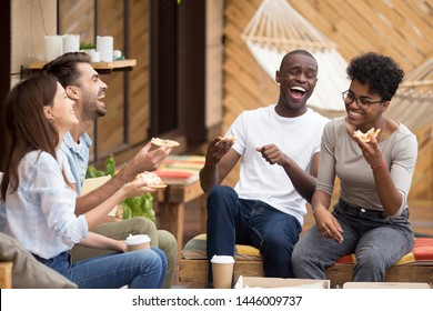Excited multiethnic millennial friends sit in restaurant outside eat delicious pizza laugh having fun, overjoyed diverse young people feel happy smiling relaxing together enjoying Italian fast food