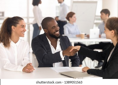 Excited multiethnic young couple shake hand with female banker get acquainted greeting at meeting, happy diverse married spouse handshake woman realtor closing successful deal. Cooperation concept