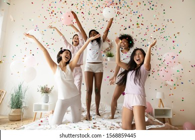 Excited multiethnic young women friends wear pyjamas dance on bed together in falling confetti having fun celebrate bachelorette bridal shower, happy ladies jump enjoy pajama birthday party concept