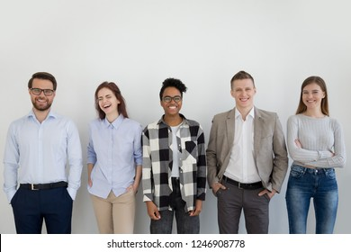 Excited multiracial millennial team standing near wall looking at camera laughing, group of young diverse employees or professionals posing, smiling business people or staff make picture in office
