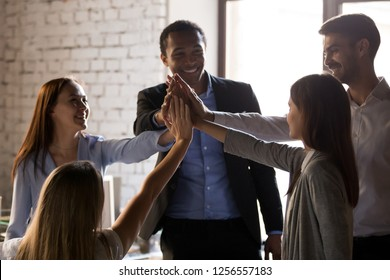 Excited multiracial team give high five, happy african and caucasian office people group celebrate good work results, motivated employees workers engaged in unity help support, teambuilding concept