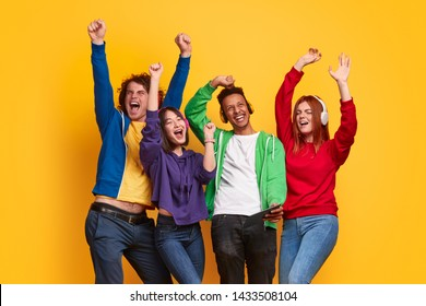 Excited multiracial young people in colorful outfits and headphones listening to music and dancing together against bright yellow background