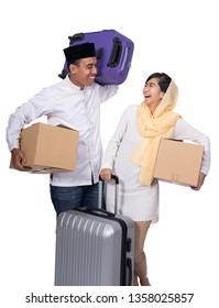 excited muslim couple with suitcase on white background. eid mubarak holiday celebration