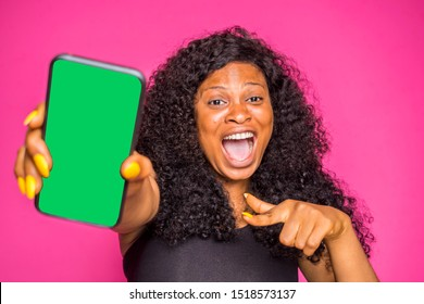 excited nigerian lady showing  and pointing to her phone screen