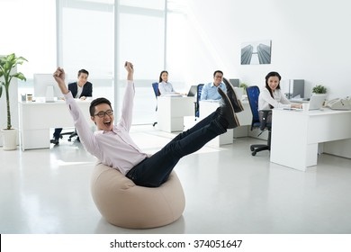 Excited office manager sitting in beanbag in center of the office