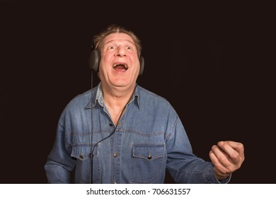 Excited old man listening to music with headphones on dark background