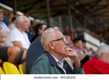 Excited old man watching sport game with open mouth. Senior people in the audience