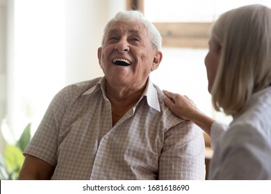 Excited older man laughing, having fun with caregiver close up, happy elderly patient satisfied by good medical checkup result, friendly mature female doctor supporting senior male, touching shoulder