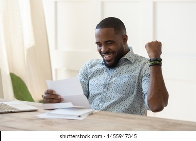 Excited overjoyed african business man student winner read postal mail letter happy with good news promotion scholarship, got new job celebrate salary rise payment taxes refund receive loan approval