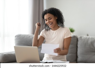 Excited overjoyed black girl student holding mail paper admission letter bank statement, happy euphoric african woman read good news get new job scholarship, celebrate loan approval great test result