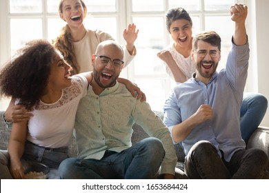 Excited overjoyed friends different ethnicity girls guys sitting on couch gathered together hanging out indoors, watching on tv sport match, supporters celebrating goal soccer fans enjoy game concept