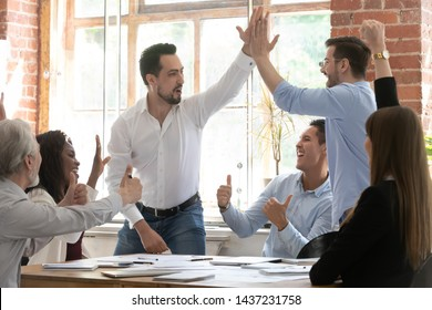 Excited overjoyed male coworkers give high five at group meeting celebrate corporate win successful teamwork result congratulate with goal achievement rejoice team reward business success in office