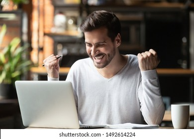 Excited overjoyed young business man student winner looking at laptop celebrate bet bid win online success victory new opportunity sit at cafe table, read good internet email news, got new job offer