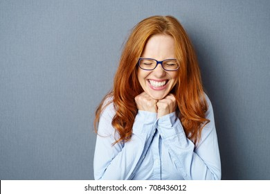 Excited overjoyed young woman wearing glasses beaming with happiness and screwing up her eyes as she holds her fists to the over a blue studio background with copy space