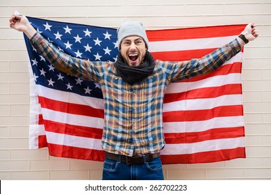 Excited patriot of American style. Excited young man holding American flag while standing against brick wall