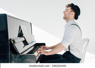 excited pianist in stylish clothing playing piano
