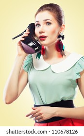 Excited pin-up girl using a shoe like a telephone holding it near her face and talking, yellow background.