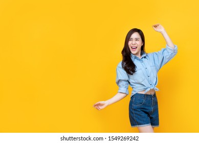 Excited pretty Asian woman smiling with arm raise isolated on yellow bakgound with copy space